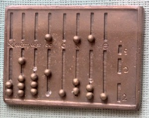 A reconstruction of a Roman hand abacus, made by the RGZ Museum in Mainz, 1977. The original is bronze and is held by the Bibliothèque nationale de France, in Paris. This example is, confusingly, missing many counter beads. Source: Wikimedia Commons